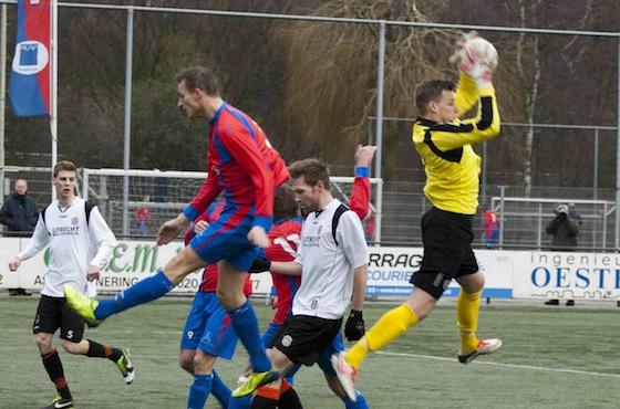 Foto Martin van Zurk: Doelman Damen plukt de bal weg voordat Alex de Bruijne kan koppen