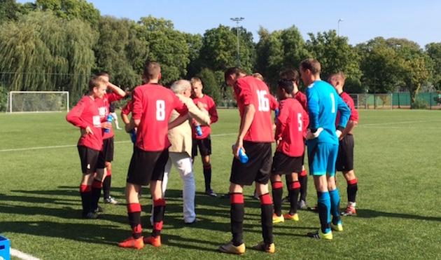 Trainer Hans Bergsma spreekt zijn spelers bemoedigend toe tijdens het competitieduel met FC Hilversum.